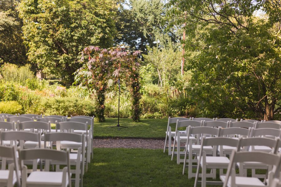 An outdoor ceremony space at Bartram's Garden, with a floral arch and white chairs set up in rows in the grass.