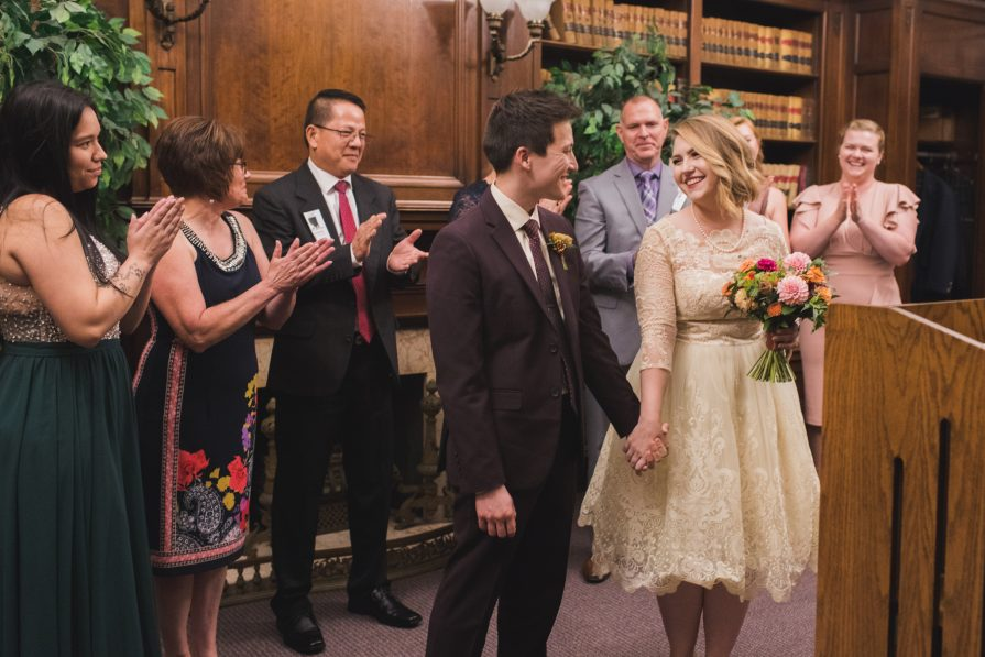 An intimate Philadelphia City Hall wedding in the courtroom. Seven guests surround the newlyweds and applaud them.