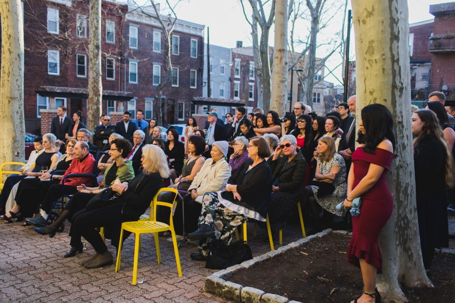 A large group of seated and standing guests at the outdoor courtyard of Fleisher Art Memorial.
