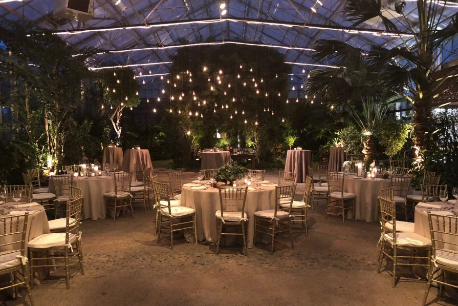 The indoor gathering space at The Horticulture Center greenhouse. The reception room is filled with tables, chairs, and hanging lights.