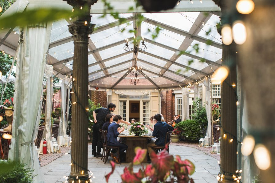 The historic outdoor, tented courtyard at Morris House Hotel, where guests are seated for dinner at an intimate microwedding.