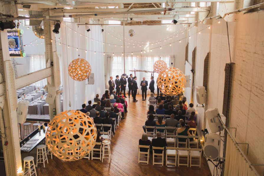 A ceremony inside Power Plant, where lights are draped above white, painted brick walls and wooden floors.