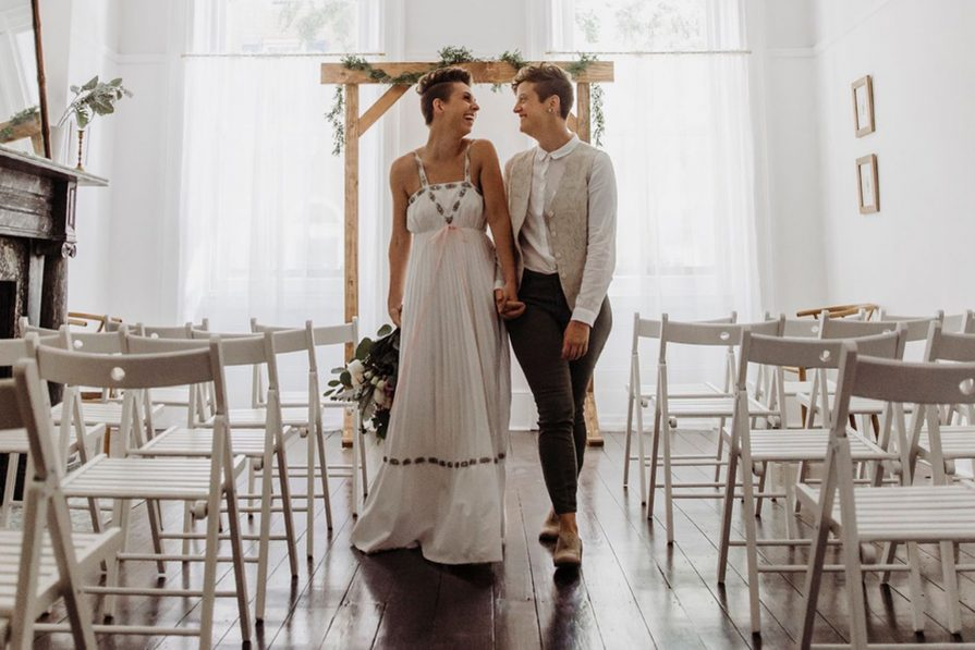 A couple stands inside Vaux Studio, an intimate wedding chapel with airy light and white folding chairs on either side of them.