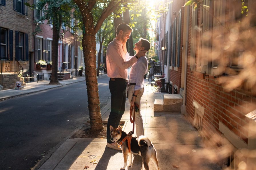 Gay couple stands with their dog at sunset in Philadelphia street.